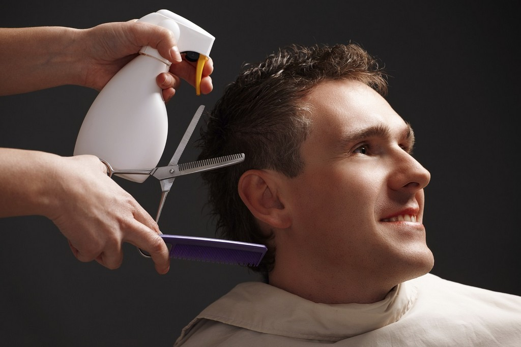 Barber cutting hair with scissors and comb, using cosmetic in spray, client is a young caucasian man